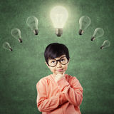 Child in thinking poses under bright light bulb Stock Images