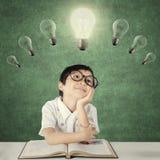 Child thinks inspiration under bright light bulb Stock Image