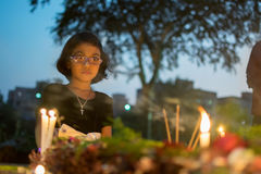 Child in thought of deceased relative. KOLKATA, WEST BENGAL , INDIA - NOVEMBER 2ND 2014 : Unknown child remembering relative at `All souls day` remembrance at stock photos