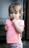 The child thought for a street. Finger in mouth. Beautiful little girl. Beautiful, beautiful baby. Stock Photo