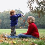 Child Throwing Autumn Leafs Stock Images