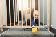 Child throwing ball away through safety gates in front of stairs. At home Royalty Free Stock Photo