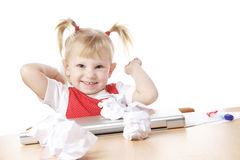 Child throwing crampled sheets of paper. At the table stock image