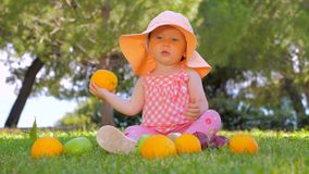 Child sitting on green grass. Child in panama having fun outdoor on back yard. Happy childhood concept. Toddler sitting. Child throwing orange while sitting on stock video footage