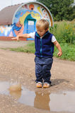 Child throwing small stone to pool Stock Image
