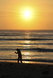 Child Throwing Stone into Ocean. Young boy throwing a stone into the ocean before sunset Royalty Free Stock Images