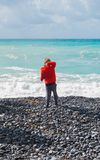 Child throwing a stone into the sea royalty free stock photos