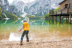Child throwing stones on lake braies in italy Stock Photo