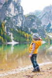 Child throwing stones while on lake braies Royalty Free Stock Images