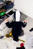 Child throws clothes. Child throws the clothes out of the closet on the floor Stock Images