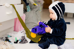 Child throws clothes. Child throws the clothes out of the closet on the floor Royalty Free Stock Photography