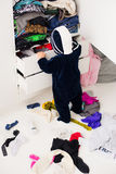 Child throws clothes. Child throws the clothes out of the closet on the floor Stock Photo