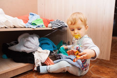 Child throws clothes Royalty Free Stock Photos