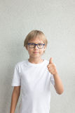 Child with thumb up over grey background. Boy with thumb up over grey background Royalty Free Stock Images