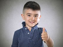 Child thumbs up. Happy child showing giving thumbs up gesture isolated on gray background Stock Photo
