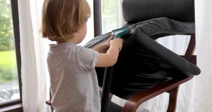 Baby boy vacuums chair. Child tidies up home vacuums chair stock footage