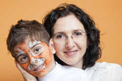 Child in tiger make-up and mother having fun Royalty Free Stock Photography