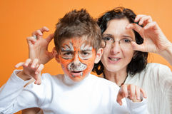 Child in tiger make-up and mother roaring Stock Photo