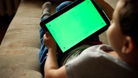 Child tilting to the left a tablet PC with green screen, back view Stock Image