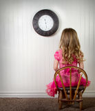 A child in time out or in trouble. A young child in time out or in trouble, with clock on wall Stock Image