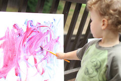 Child, Toddler Fingerpainting. Toddler boy, child, drawing, finger painting, making art Royalty Free Stock Photos