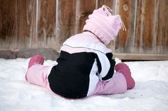 Child, Toddler girl dressed in pink playing in winter snow. Stock Images