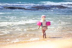 Child toddler girl in swimwear on beach standing in front of storming sea and ready to swim in during summer vacation concept fear stock photo