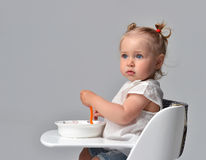 Child toddler kid sitting with plate and spoon on white baby cha Royalty Free Stock Photography