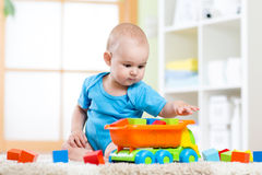 Child toddler playing wooden toys at home Royalty Free Stock Photos
