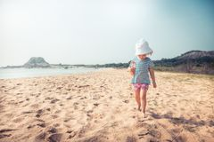 Child toddler walking beach summer holidays vacation childhood traveling lifestyle. Child toddler walking beach summer holidays vacation concept for childhood royalty free stock photography
