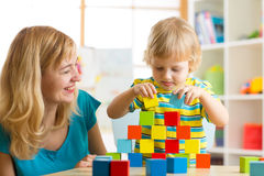 Child together with mom playing educational toys at home Stock Images