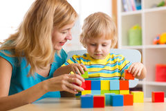 Child together with mother playing educational toys Royalty Free Stock Photos