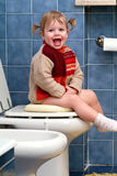 Child on the toilet. Little girl on the toilet that makes funny faces royalty free stock images