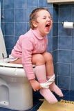 Child on the toilet. Little girl on the toilet that makes funny faces stock photography