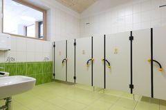 Child toilets in kindergarten with nice green gras. Toilet with small doors for children with nice decorated grass tiles Stock Photo