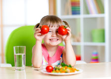 Child with tomatoes. Happy girl with vegetables at Stock Photos