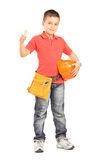Child with tool belt holding a helmet  and giving a thumb up Stock Image