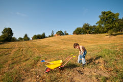Child with tools and wheelbarrow Stock Photos