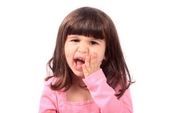 Child with toothache. Cute young four year old child holding her cheek with a toothache stock photo
