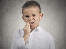 Child with toothache. Child toothache. Closeup portrait boy with sensitive tooth ache crown problem touching outside mouth with hand isolated grey wall royalty free stock photo