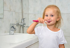 Child with toothbrush washes Stock Image