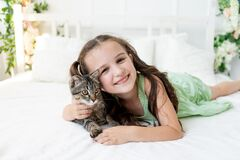 A child is torturing an animal, a little girl with a cat is lying on the bed, the concept of a child`s friendship with animals