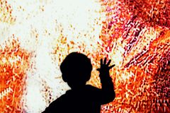 Child touch the big screen. Child hand touches on the colored glass stock photo