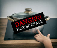 Child touches hot pan. Child touches hot pan on the stove. Dangerous situation at home Stock Images