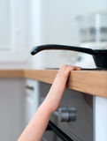 Child touches hot pan on the stove. Dangerous situation at home stock images