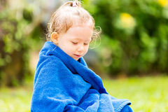 Child in towel after swimming basking in sun on tropical resort Royalty Free Stock Image