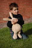A child and a toy. Little boy with a toy hare in hands Stock Images