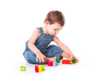 Child with a toy. Baby playing with color blocks isolated on white Royalty Free Stock Photo