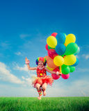 Child with toy balloons in spring field Royalty Free Stock Images