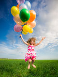 Child with toy balloons in spring field Stock Photography